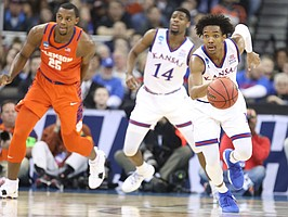 Kansas guard Devonte' Graham (4) runs up the court with the ball during the first half, Friday, March 23, 2018 at CenturyLink Center in Omaha, Neb.