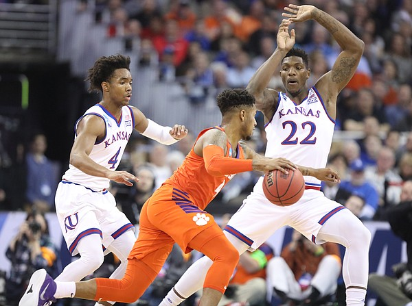 Kansas guard Devonte' Graham (4) and Kansas forward Silvio De Sousa (22) defend as Clemson guard Shelton Mitchell (4) drives during the first half, Friday, March 23, 2018 at CenturyLink Center in Omaha, Neb.