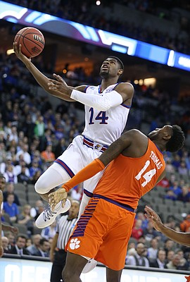 Kansas guard Malik Newman (14) swoops in for a bucket against Clemson forward Elijah Thomas (14) during the first half, Friday, March 23, 2018 at CenturyLink Center in Omaha, Neb.
