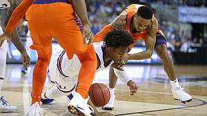 Kansas guard Devonte' Graham (4) hits the ground for a ball with Clemson guard Marcquise Reed (2) during the first half, Friday, March 23, 2018 at CenturyLink Center in Omaha, Neb.