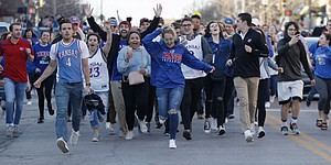 Shortly after the end of the KU-Duke game, Jayhawk fans run out of bars and down Massachusetts St., to celebrate Sunday, March 25, after the KU men's basketball team's NCAA tournament win over Duke Sunday to advance to the Final Four next week in San Antonio, TX.