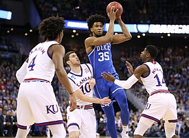 Kansas guard Sviatoslav Mykhailiuk (10) and Kansas guard Malik Newman (14) pressure Duke forward Marvin Bagley III (35) during the first half, Sunday, March 25, 2018 at CenturyLink Center in Omaha, Neb.