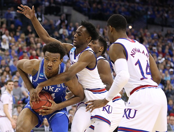 Kansas guard Marcus Garrett (0) fouls Duke forward Wendell Carter Jr (34) during the first half, Sunday, March 25, 2018 at CenturyLink Center in Omaha, Neb.
