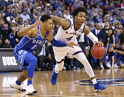 Kansas guard Devonte' Graham (4) drives against Duke guard Trevon Duval (1) during the second half, Sunday, March 25, 2018 at CenturyLink Center in Omaha, Neb.