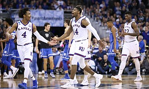 Kansas guard Devonte' Graham (4) and Kansas guard Malik Newman (14) celebrate a three in overtime by Newman, Sunday, March 25, 2018 at CenturyLink Center in Omaha, Neb.