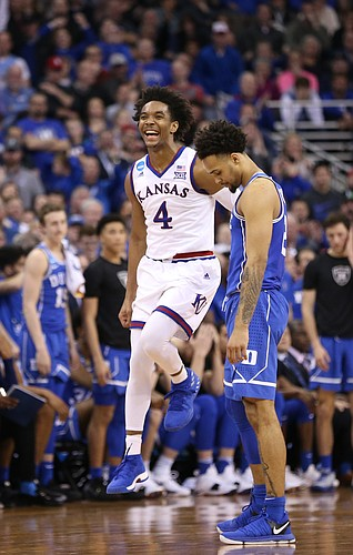 A giddy Kansas guard Devonte' Graham (4) jumps as the Jayhawks begin to secure the victory in overtime, Sunday, March 25, 2018 at CenturyLink Center in Omaha, Neb.