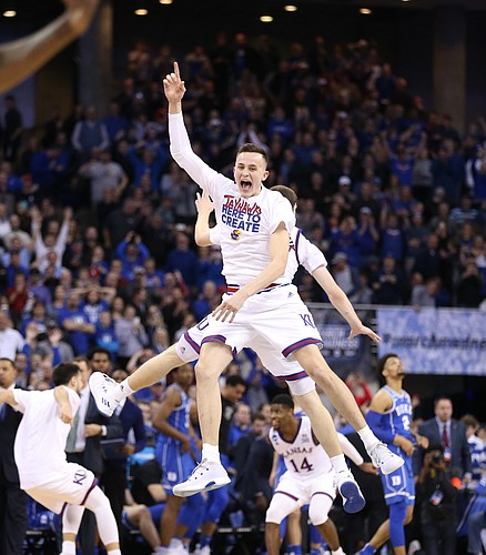 Kansas forward Mitch Lightfoot and Kansas guard Sviatoslav Mykhailiuk (10) celebrate in midair as the seconds after beating Duke in overtime to go to the Final Four on Sunday in Omaha, Neb.
