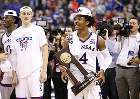 Kansas guard Devonte' Graham (4) holds the Midwest Regional trophy as the Jayhawks celebrate a trip to the Final Four following their 85-81 overtime victory over Duke on Sunday in Omaha, Neb.