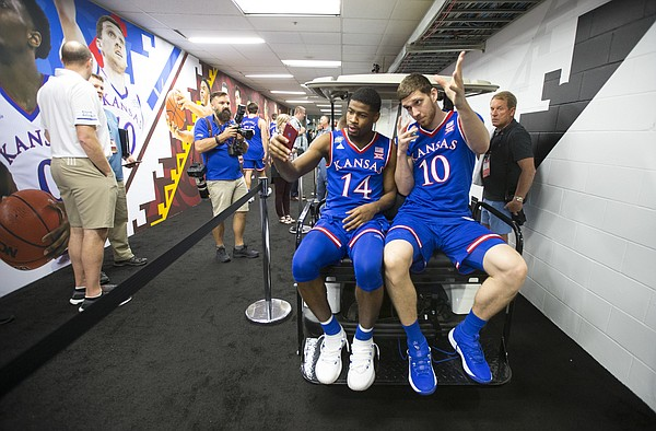 Kansas guard Malik Newman (14) records a video of himself and Kansas guard Sviatoslav Mykhailiuk (10) catching a lift on a golf cart to interviews with CBS on Thursday, March 29, 2018 at the Alamodome in San Antonio, Texas.