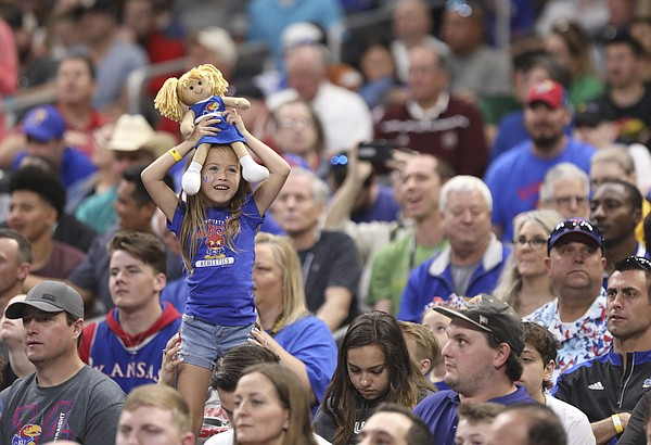 Kansas fan Bristyn Young, San Antonio, hoists up a KU cheerleader doll as she watches the Jayhawks' practice on Friday, March 30, 2018 at the Alamodome in San Antonio, Texas.