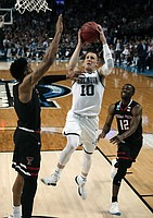 Villanova's Donte DiVincenzo, center, drives between Texas Tech's Justin Gray, left, and Keenan Evans, right, during the first half of an NCAA men's college basketball tournament regional final, Sunday, March 25, 2018, in Boston.