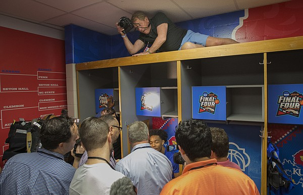 In a tightly-packer locker room, Kansas Athletics photographer Jeff Jacobsen steadies himself above the locker of Devonte' Graham to get a fisheye view as media members talk with Graham on Thursday, March 29, 2018 at the Alamodome in San Antonio.