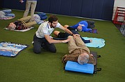 Phillip Palmer, an intern at LMH Therapy Services, assists Lew Phillips with stretches during a recent exercise class designed specifically for people with Parkinson's disease. The classes are held twice a week at Sports Pavilion Lawrence.