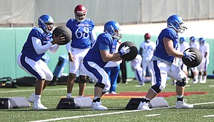 Kansas offensive lineman Chris Hughes (76), left, Beau Lawrence (60) and Hunter Saulsbury (66) work through a drill during practice on Wednesday, April 4, 2018.