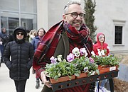 British artist Paul Harfleet carries a tray of pansies as he sets off to plant several of them on the University of Kansas campus as part of his Pansy Project, Friday, April 6, 2018. Harfleet planted several pansies in various spots on the KU campus associated with homophobic abuse or homophobic incidents.