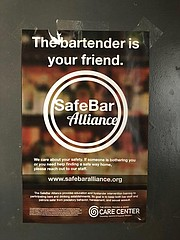 A SafeBar Alliance sign, located in the Burger Stand restroom, encourages staff and patrons to seek help if they are made uncomfortable in the restaurant.