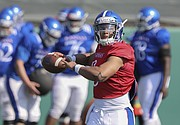 Kansas sophomore quarterback Miles Kendrick pulls back to throw during practice on Tuesday, April 10, 2018.