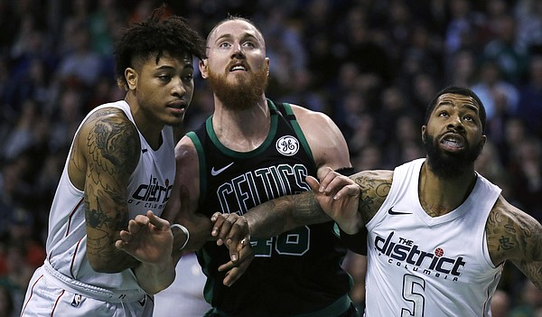 Boston Celtics center Aron Baynes, center, and Washington Wizards forwards Markieff Morris (5) and Kelly Oubre Jr., left, wait for a rebound during the first quarter of an NBA basketball game in Boston, Wednesday, March 14, 2018. (AP Photo/Charles Krupa)