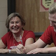 Lawrence High senior Stephen Johnson signs his national letter of intent on Wednesday in the LHS library to swim at the University of South Dakota.