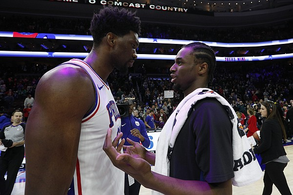 Minnesota Timberwolves' Andrew Wiggins, right, talks things over with Philadelphia 76ers' Joel Embiid, of Cameroon, following the second half of an NBA basketball game, Saturday, March 24, 2018, in Philadelphia. The 76ers won 120-108. (AP Photo/Chris Szagola)
