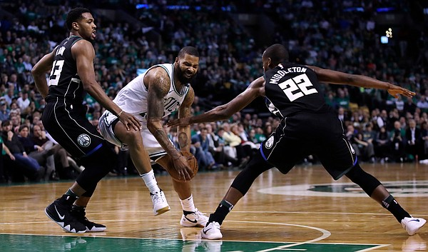 Boston Celtics forward Marcus Morris, center, drives to the basket between Milwaukee Bucks forward Khris Middleton (22) and guard Sterling Brown, right, during the fourth of Game 2 of an NBA basketball first-round playoff series in Boston, Tuesday, April 17, 2018. The Celtics defeated the Bucks 120-106. (AP Photo/Charles Krupa)