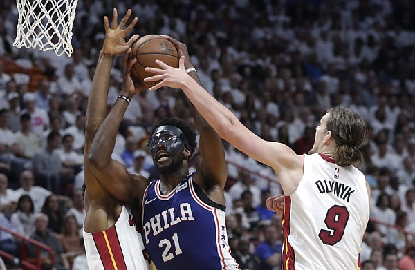 Philadelphia 76ers' Joel Embiid (21) drives to the basket as Miami Heat's Hassan Whiteside, left, and Kelly Olynyk (9) defend during the first half of Game 3 of a first-round NBA basketball playoff series Thursday, April 19, 2018, in Miami. (AP Photo/Lynne Sladky)