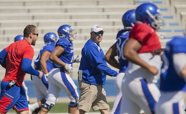 First-year Kansas offensive line coach A.J. Ricker watches over his position players during warmups at practice on Monday, April 23, 2018.
