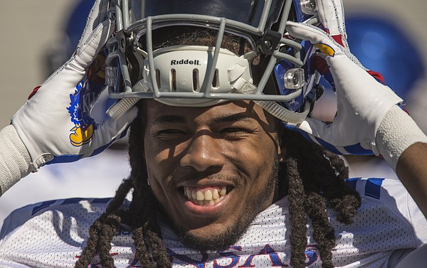Kansas freshman cornerback Corione Harris smiles as he pulls on his helmet during practice on Monday, April 23, 2018.