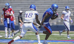 Kansas wide receiver Daylon Charlot (2) gets past Kansas linebacker Denzel Feaster (18) during an open practice on Saturday, April 28, 2018 at Memorial Stadium.