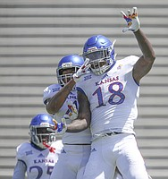 Kansas linebacker Denzel Feaster (18) celebrates a hit during an open practice on Saturday, April 28, 2018 at Memorial Stadium.