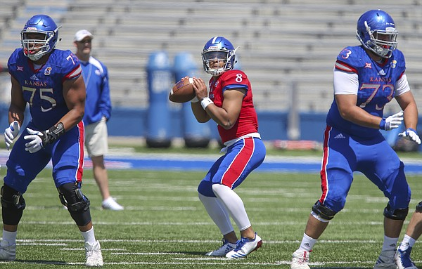 Kansas quarterback Miles Kendrick drops back to throw as he is protected by Kansas offensive lineman Antione Frazier (75) and Kansas offensive lineman Larry Hughes (73) during an open practice on Saturday, April 28, 2018 at Memorial Stadium.