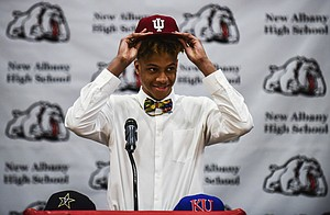 Romeo Langford places an Indiana University cap onto his head after selecting to continue his basketball career with the Hoosiers on Monday at New Albany High School, Monday, April 30, 2018, in New Albany, Ind.