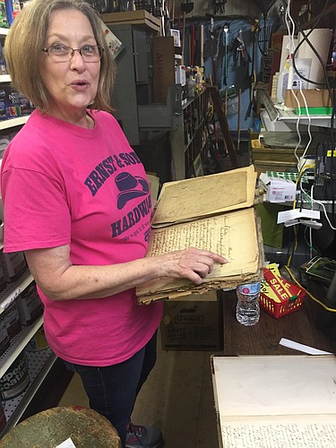 "Lynda Allen holds the ""correspondence book"" from Ernst & Son Hardware, while the store's original business ledger dating back to 1905 rests on the table."