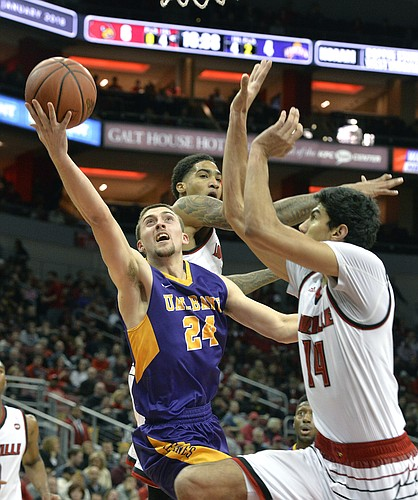 Albany guard Joe Cremo (24) attempts a layup past the defense of Louisville forward Ray Spalding (13), and forward Anas Mahmoud (14) during the first half of an NCAA college basketball game, Wednesday, Dec. 20, 2017, in Louisville, Ky.