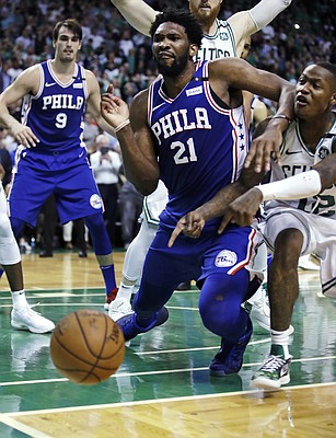 Philadelphia 76ers center Joel Embiid (21) drops to the floor as the ball bounces out of bounds after hitting him, as Boston Celtics guard Terry Rozier, right, points during the final seconds of Game 5 of an NBA basketball playoff series in Boston, Wednesday, May 9, 2018. The turnover helped the Celtics keep the lead as they defeated the 76ers 114-112. (AP Photo/Charles Krupa)
