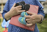 Mary Tye holds shoes from two of her former foster children.