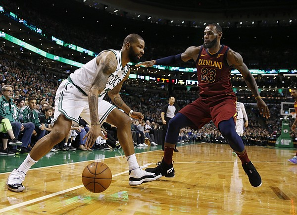Boston Celtics forward Marcus Morris (13) makes a dribble move against Cleveland Cavaliers forward LeBron James (23) during the second half of Game 1 of the NBA basketball Eastern Conference Finals, Sunday, May 13, 2018, in Boston. (AP Photo/Michael Dwyer)