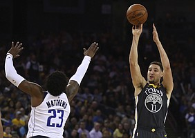 Golden State Warriors' Klay Thompson, right, shoots over Dallas Mavericks' Wesley Matthews (23) during the second half of an NBA basketball game Thursday, Feb. 8, 2018, in Oakland, Calif. (AP Photo/Ben Margot)