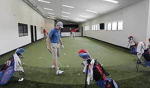 KU senior Daniel Sutton, foreground, and other members of the KU golf team practice putting inside the new KU golf facility at the Jayhawk Club, formerly the Alvamar Country Club. The team is the 15th seed in the NCAA Men's Golf Championships, which begin Friday in Stillwater, Okla.