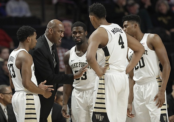 FILE — Wake Forest head coach Danny Manning, second from left, talks to his team during the first half of an NCAA college basketball against Tennessee in Winston-Salem, N.C., Saturday, Dec. 23, 2017. (AP Photo/Chuck Burton)