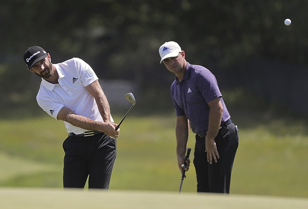 Dustin Johnson chips onto the second green as Gary Woodland looks on during a practice round for the U.S. Open Golf Championship, Monday, June 11, 2018, in Southampton, N.Y. (AP Photo/Julie Jacobson)