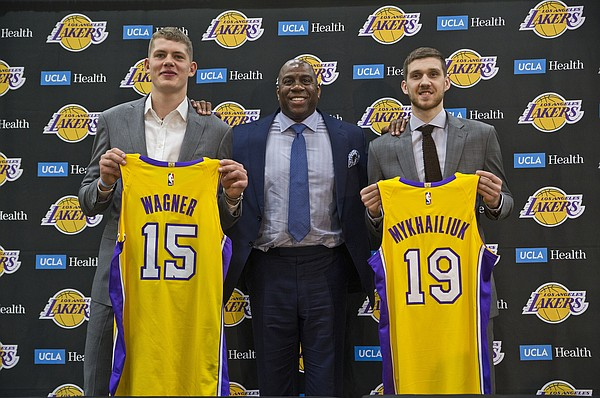 "Los Angeles Lakers president of basketball operations, Earvin ""Magic"" Johnson, center, poses with Moritz Wagner, left, and Sviatoslav Mykhailiuk during a press conference to introduce the Lakers draft picks, in El Segundo, Calif., Tuesday, June 26, 2018. Magic Johnson is betting his job on his free-agent recruiting skills for the Los Angeles Lakers. Johnson says he will step down as the Lakers' president of basketball operations if he can't persuade an elite free agent to sign with his club within the next two summers. (AP Photo/Damian Dovarganes)"