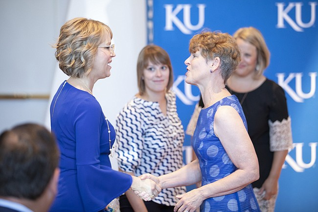 Fanny Long, wife of new University of Kansas athletic director Jeff Long, left, is greeted by Susan Girod, wife of University of Kansas Chancellor Douglas Girod as the two sit for Jeff Long's introductory news conference on Wednesday, July 11, 2018 at the Lied Center Pavilion.