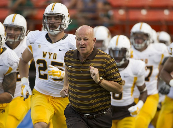 Wyoming head coach Craig Bohl leads his team onto the field before their NCAA college football game against Hawaii, Saturday, Oct. 11, 2014, in Honolulu. (AP Photo/Eugene Tanner)