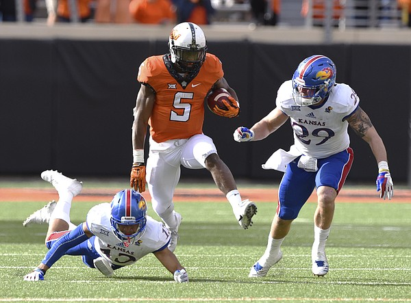 Oklahoma St running back Justice Hill (5) runs between Kansas corner back Hasan Defense (13) and linebacker Joe Dineen Jr. (29) during the second half of a NCAA college football game in Stillwater, Okla., Saturday, Nov. 25, 2017. Hill led Oklahoma St rushing with 58 yards in the 58-17 win over Kansas.