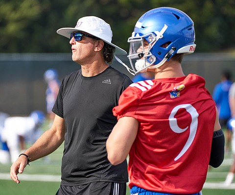 Kansas football offensive coordinator and quarterbacks coach Doug Meacham and quarterback Carter Stanley watch as a drill plays out in front of them during a preseason practice on Aug. 4, 2018.