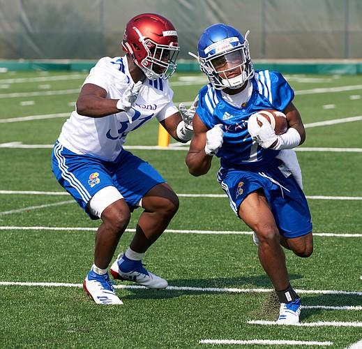 Kansas freshman running back Pooka Williams scoots past senior linebacker Osaze Ogbebor during practice drills on Aug. 4, 2018