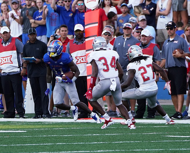 Kansas wide receiver Steven Sims (11) put a move on Nicholls State defensive backs Khristian Mims (34) and Jonavon Lewis (27) during the first half on Saturday, Sept. 1, 2018 at Memorial Stadium.
