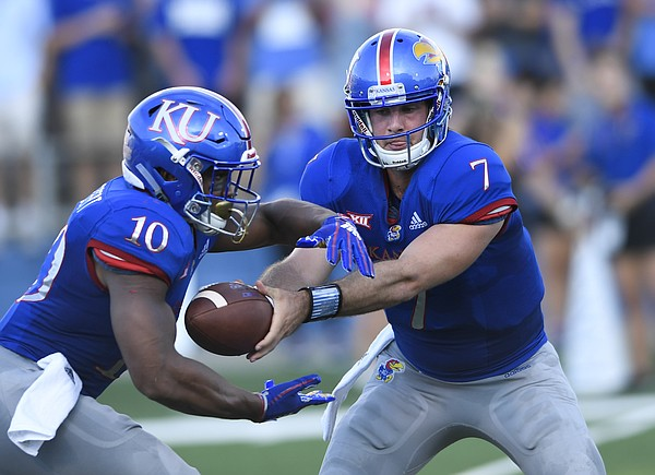 Kansas quarterback Peyton Bender (7) hands off to running back Khalil Herbert (10) during the first quarter of an NCAA college football game in Lawrence, Kan., Saturday, Sept. 1, 2018. (AP Photo/Reed Hoffmann