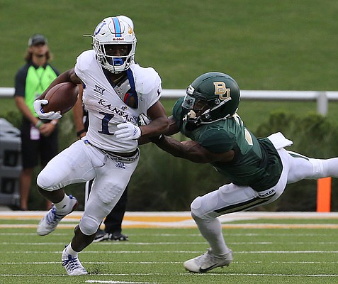 Kansas running back Pooka Williams Jr. (1) breaks the tackle of Baylor safety Chris Miller (3) during the first half of an NCAA college football game, Saturday, Sept. 22, 2018, in Waco, Texas.